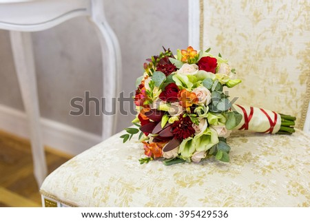 beautiful bouquet of colorful flowers and green roses lying on a chair close-up - stock photo