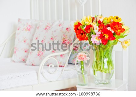 Beautiful bouquet of colorful tulips in interior of child room - stock photo
