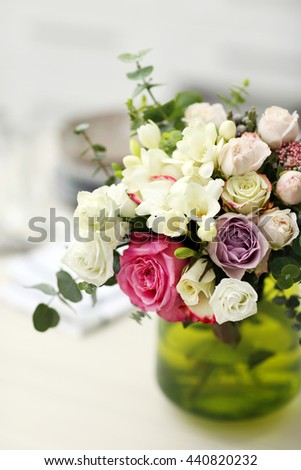 Beautiful bouquet of colourful roses in glass vase on the kitchen table - stock photo