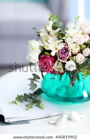 Beautiful bouquet of colourful roses in glass vase on white table - stock photo