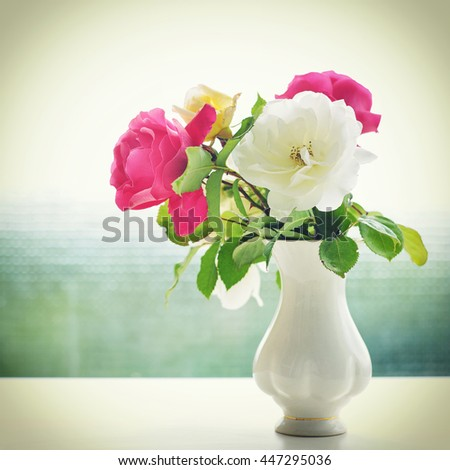 Beautiful bouquet of cream and pink rose flowers in vase with green bokeh background. - stock photo