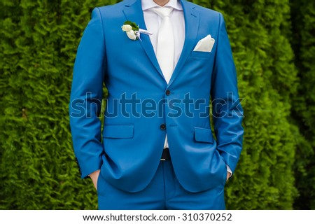 Beautiful bouquet of flowers ready for the big wedding ceremony. adult solid groom and his blue suit  - stock photo