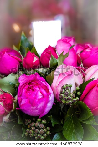 Beautiful bouquet of magenta and pink roses and peonies with blank paper attached. Valentines day greeting card. Selective focus and shallow depth of field. Bleached angles. - stock photo