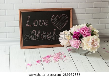 Beautiful bouquet of pink and white peonies in the glass vase with petals and black chalkboard with inscription Love You on the light grey brick and wood background. - stock photo
