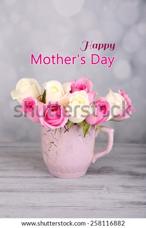 Beautiful bouquet of pink and white roses in cup on wooden table - stock photo
