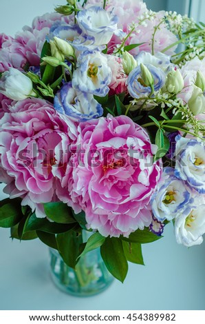 Beautiful bouquet of pink peonies, roses, eustoma flowers in vase on white window sill, cream color background. Spring or summer lovely bouquet. Fresh floral, home decor. Text, copy space - stock photo