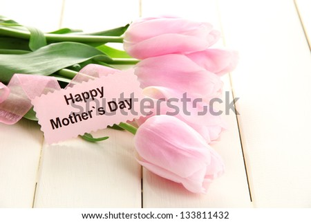 Beautiful bouquet of pink tulips for Mother's Day on white wooden background - stock photo