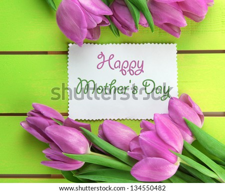 Beautiful bouquet of purple tulips and card on green wooden background - stock photo