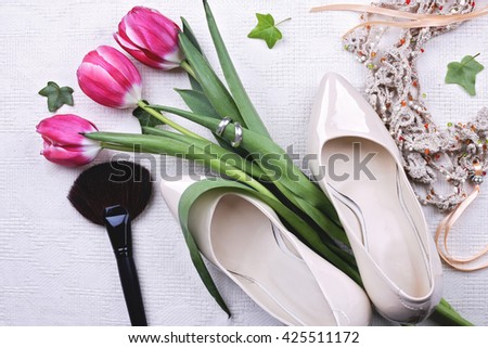 Beautiful bouquet of tulips with two silver wedding rings, creamy high heels shoes, handmade knitted necklace and makeup brush on the table in the room - stock photo