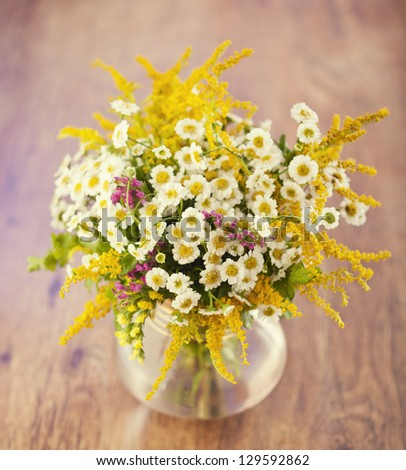 Beautiful bouquet of wild flowers on wooden table - stock photo