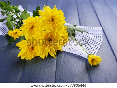 Beautiful bouquet of yellow chrysanthemum with napkin on wooden table - stock photo