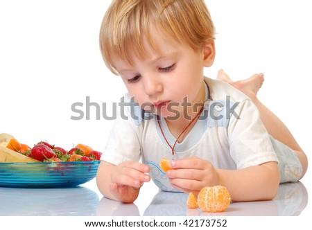 beautiful boy eating fruits isolated on white.
