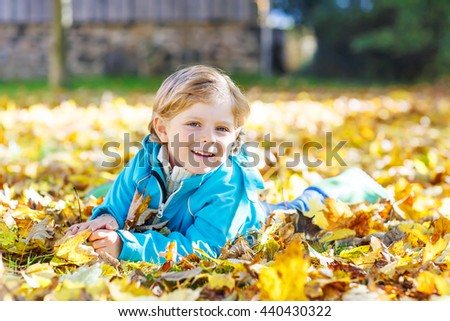 Beautiful boy, little child laying with a lot of yellow autumn leaves in park. Kid boy having fun on sunny warm october day. Season, children, lifestyle concept - stock photo