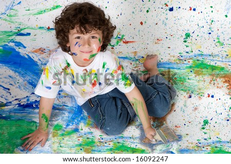 Beautiful boy playing with painting with the background painted - stock photo