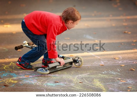 Beautiful boy riding a scooter, fall from the scooter - stock photo