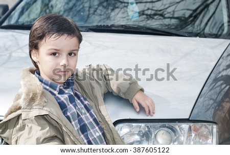 beautiful boy standing near a car