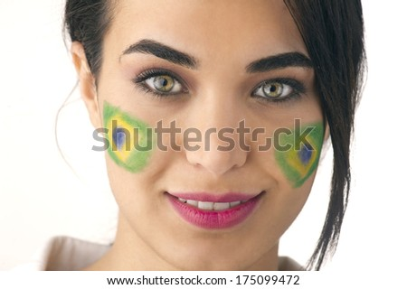 beautiful brazilian supporter with flags on her face posing for the camera - stock photo