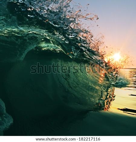 beautiful breaking glossy ocean wave crashing near the beach at sunset. - stock photo