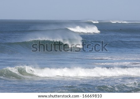 beautiful breaking waves in a row with some sea spray
