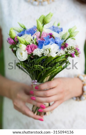 Beautiful bridal bouquet of flowers in hands of young bride