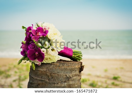 Beautiful bridal bouquet of white roses and orchids on a background of the sea. - stock photo