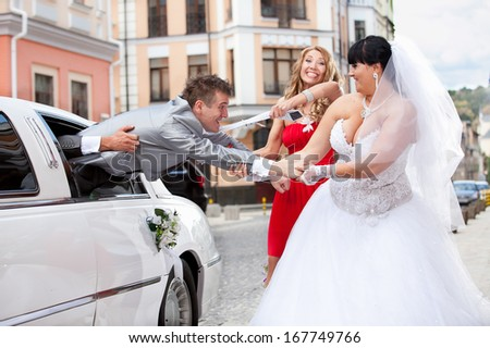 Beautiful bride and bridesmaid pulling groom out of car window - stock photo