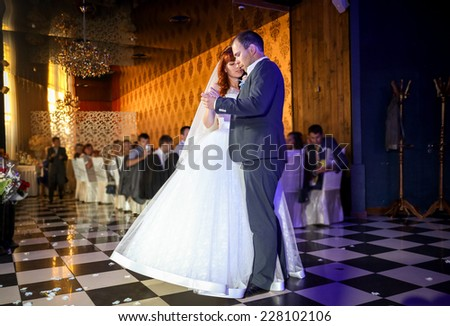 Beautiful bride and groom dancing at restaurant banquet hall - stock photo