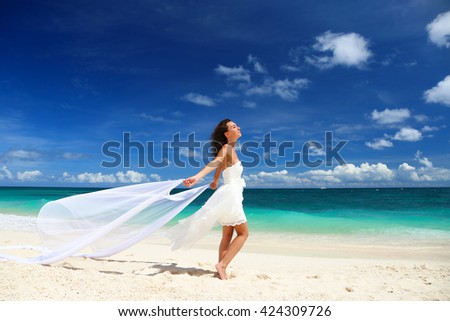 Beautiful bride and groom having fun on sandy tropical beach. Beach wedding concept - stock photo