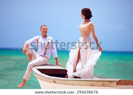 beautiful bride and groom in boat swimming at caribbean sea - stock photo