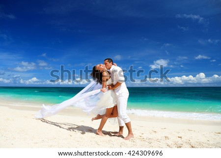 Beautiful bride and groom kissing on white sand tropical beach. Beach wedding concept - stock photo