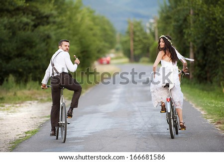Beautiful bride and groom riding on the bikes - stock photo