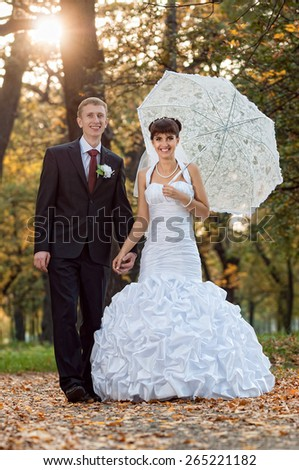 Beautiful bride and groom walking in a park