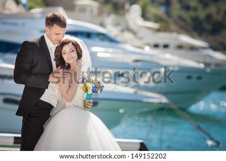 Beautiful bride and groom wedding couple dancing near sea yacht. Happy newlywed couple at wedding. Cheerful married couple standing on the beach. Monaco wedding. Cote de azure Gorgeous wedding outdoor - stock photo