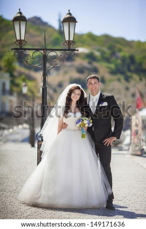 Beautiful bride and groom wedding couple dancing near sea yacht. Happy newlywed couple at wedding. Cheerful married couple standing on the beach. Monaco wedding. Cote de azure Gorgeous wedding outdoor - stock photo