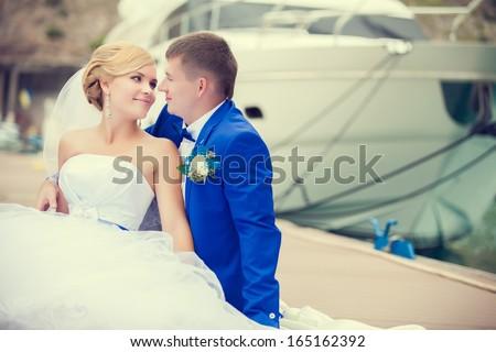 Beautiful bride and groom wedding couple near sea yacht. Happy newlywed couple at wedding. Cheerful married couple standing on the beach. Monaco wedding. Cote de azure Gorgeous wedding outdoor - stock photo