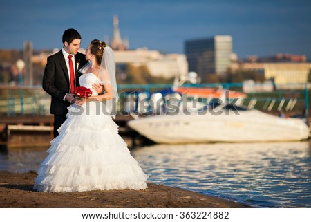 Beautiful bride and groom wedding couple near sea yacht. Happy newlywed couple at wedding. Cheerful married couple standing on the beach. - stock photo