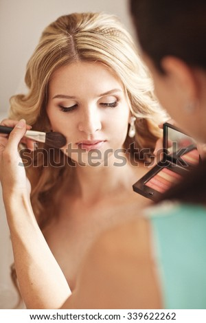 Beautiful bride applying wedding make-up by professional make-up artist on the wedding day at home  - stock photo