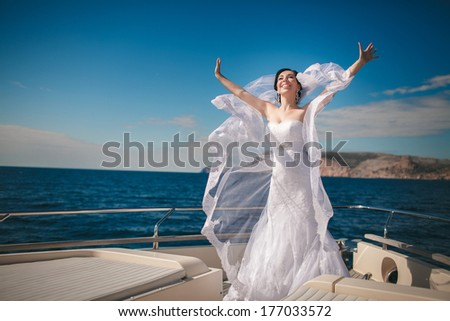 Beautiful Bride at Wedding day at luxury yacht at sea, happy newlywed woman outdoors in wedding dress and veil. Marriage day emotional moments. Series. - stock photo