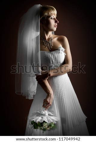 Beautiful bride, blonde posing in studio on dark background