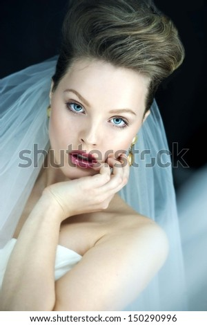 beautiful bride brunette girl in white wedding dress with hairstyle and bright makeup looks in the mirror  - stock photo