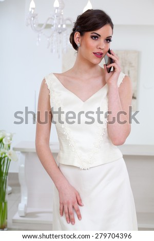 Beautiful bride chooses a wedding dress and stories using a mobile phone - stock photo