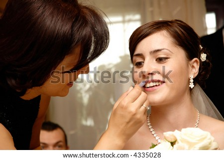 Beautiful bride having her makeup done - stock photo