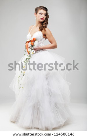 beautiful bride in a luxurious wedding dress, studio shot - stock photo