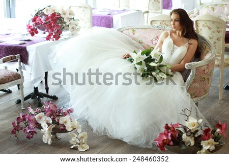 Beautiful bride in a magnificent white wedding dress of tulle with a corset sitting on the sofa with bouquet lily and orchid - stock photo