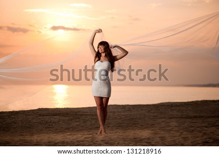 Beautiful bride in a short dress with a long veil on the beach at sunset - stock photo