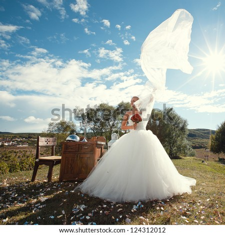 beautiful bride in a white wedding dress posing outdoors with a bouquet of roses - stock photo