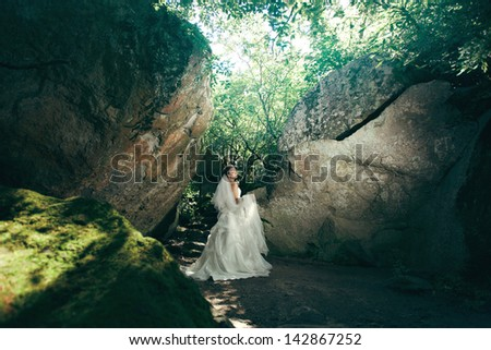 beautiful bride in a white wedding dress walking in the forest outdoors