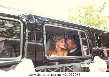 Beautiful bride in black car
