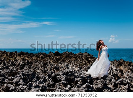 Beautiful bride in his dreams standing on a reef near the ocean - stock photo