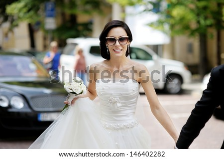 Beautiful bride in sunglasses posing in a city